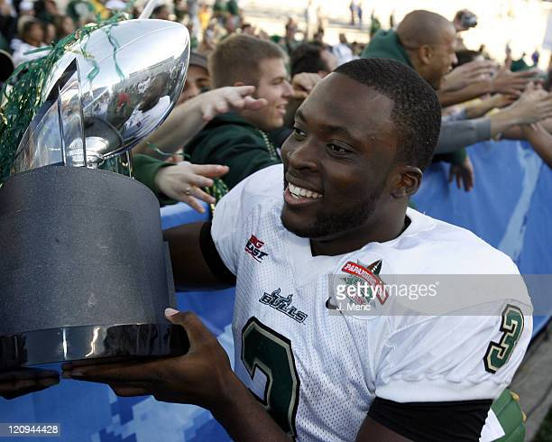 South Florida quarterback Pat Julmiste shows the PapaJohnscom Bowl Trophy to the fans after Saturday's victory over East Carolina at Legion Field in...