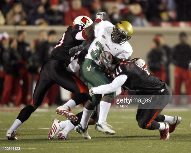 South Florida's Ben Williams is tackled by a pair of Louisville defenders in Saturday night's game at Papa John's Cardinal Stadium in Louisville...