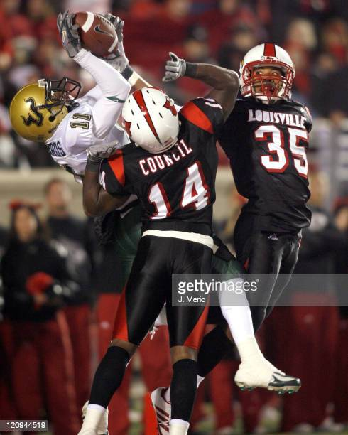 South Florida's Marcus Edwards goes up after the ball as Louisville's Rod Council and Brandon Sharp break up this play during Saturday night's game...