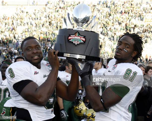 South Florida's Pat Julmiste and SJ Green hoist the PapaJohnscom Bowl Trophy after Saturday's victory over East Carolina at Legion Field in...