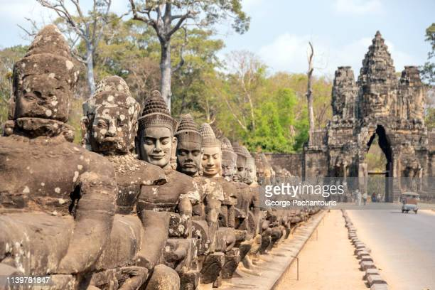 south gate bridge in angkor thom temple, cambodia - khmer art stock photos and pictures