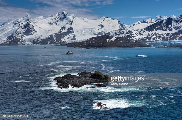 south georgia, island in sea with snowcapped mountains in background, aerial view - zuid georgia eiland stockfoto's en -beelden
