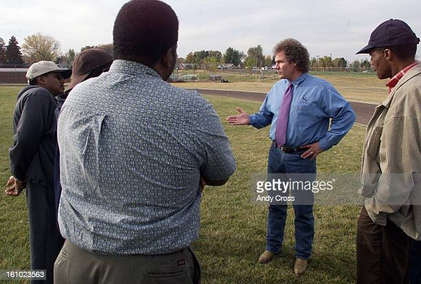 South High School principal, Shawn Batterberry, talks with parents of South High football players during practice Friday afternoon about the...