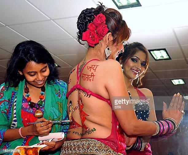 South Indian actress Tanisha Singh poses as artist Poonam Salecha paits during a backless Body painting photo shoot for a Dandiya Raas folk dance as...