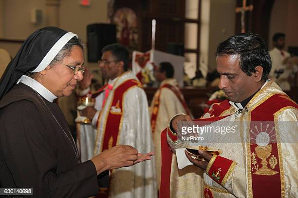 South Indian Catholic priest offers a nun a Catholic wafer during the anniversary of the 1st Episcopal Ordination of Bishop Jose Kalluvelil in...