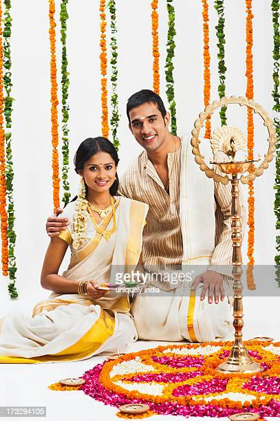 South Indian couple near a rangoli of flowers at Onam