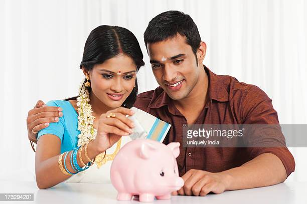 South Indian couple putting cash in a piggy bank