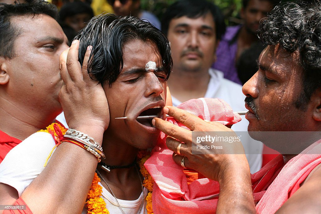 South Indian devotee gets his cheek pierced with a metal rod while participating in a religious procession to praise the Hindu goddess Shetala Mata...