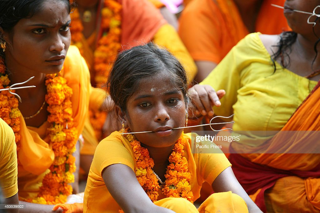 South Indian devotees gets their tongues pierced with metal rods while participating in a religious procession to praise the Hindu goddess Shetala...