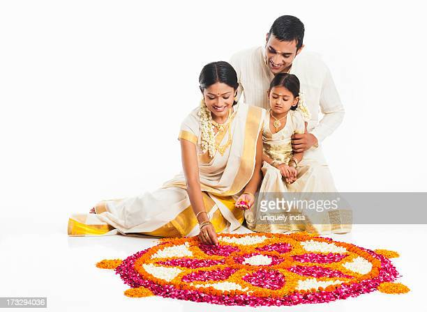 South Indian family making a rangoli of flowers at Onam