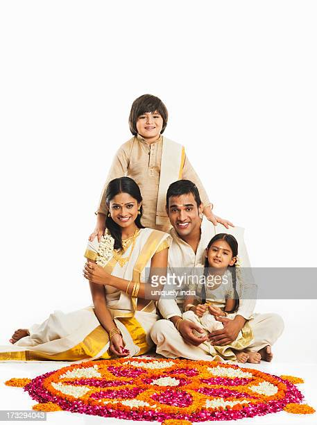 south indian family making a rangoli of flowers at onam - rangoli stock pictures, royalty-free photos & images