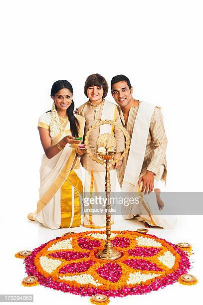 South Indian family standing near rangoli of flowers at Onam