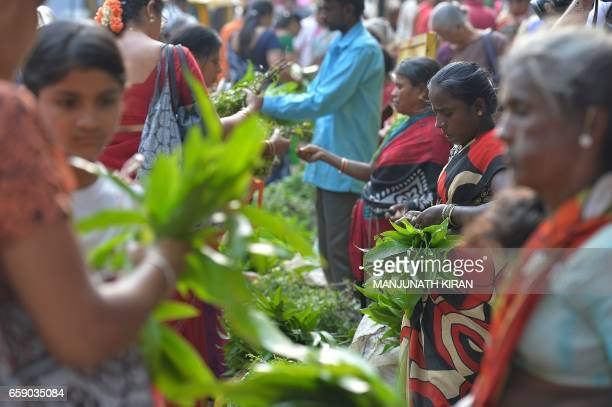 South Indian Hindus buy mango and neem leaves used during events to mark the Hindu New Year at a market in Bangalore on March 28 2017 The Hindu New...
