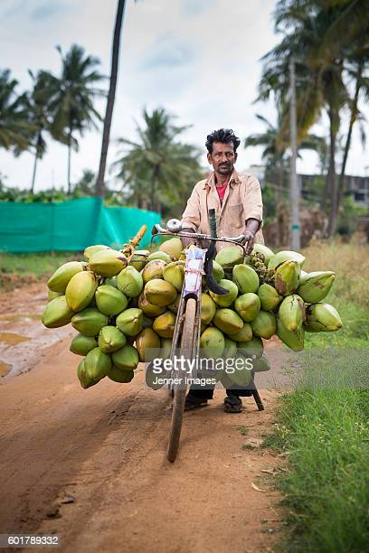South Indian man carrying coconuts on his bicycle.