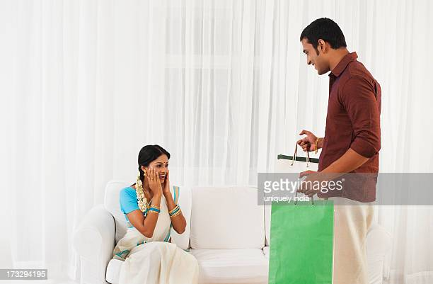 South Indian man carrying shopping bags and his wife looking shocked