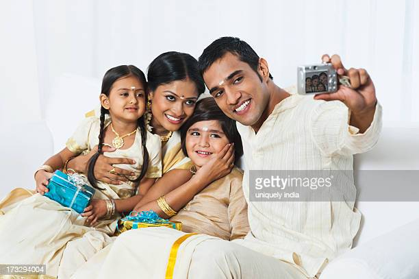 South Indian man taking a picture of his family at Onam