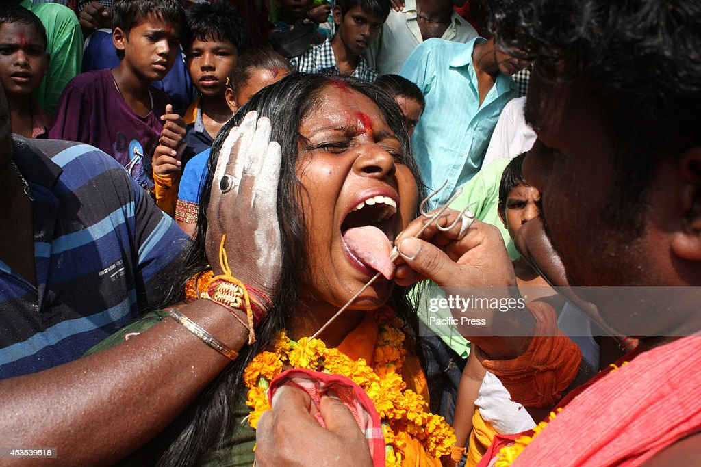 South Indian woman devotee gets her tongue pierced with a metal rod while participating in a religious procession to praise the Hindu goddess Shetala.