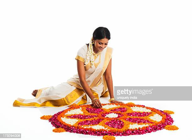 South Indian woman making a rangoli of flowers at Onam