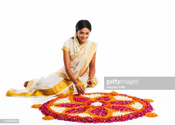 south indian woman making a rangoli of flowers at onam - rangoli stock pictures, royalty-free photos & images