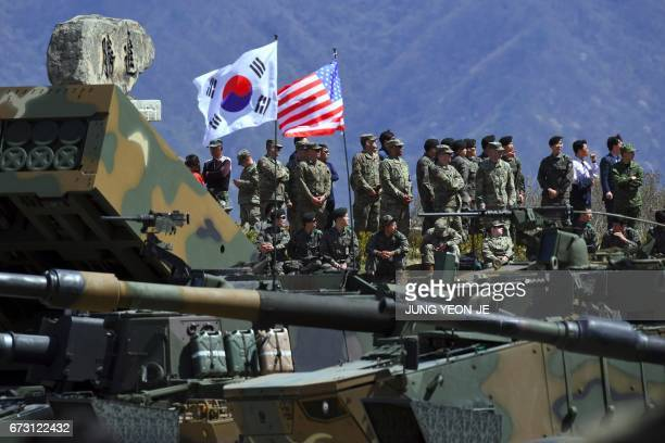 South Korea and US soldiers watch from an observation post during a joint live firing drill between South Korea and the US at the Seungjin Fire...