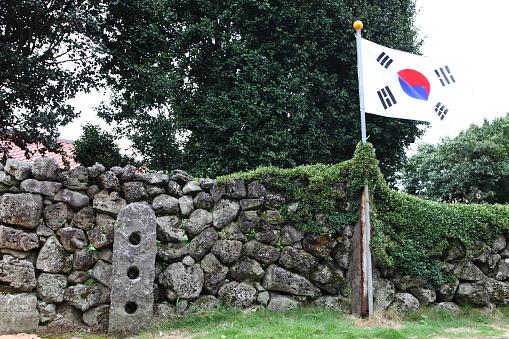 South Korea flag next to traditional stone wall at Seongeup Folk Village - gettyimageskorea