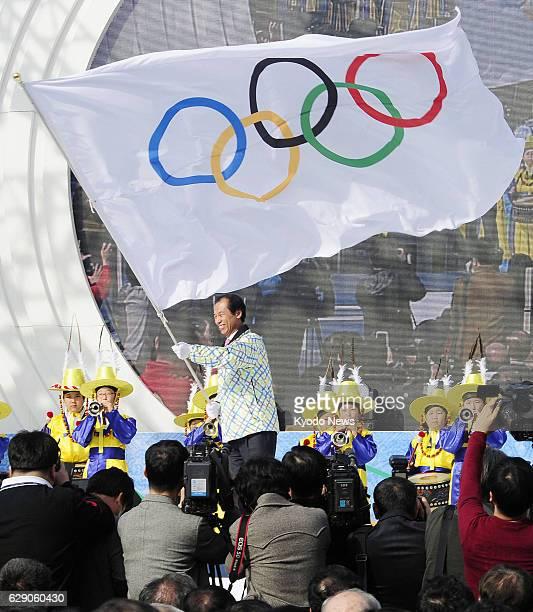 CHUNCHEON South Korea Gangwan Province Gov Choi Moon Soon waves the Olympic flag during a ceremony in the provincial capital of Chuncheon on Feb 26...