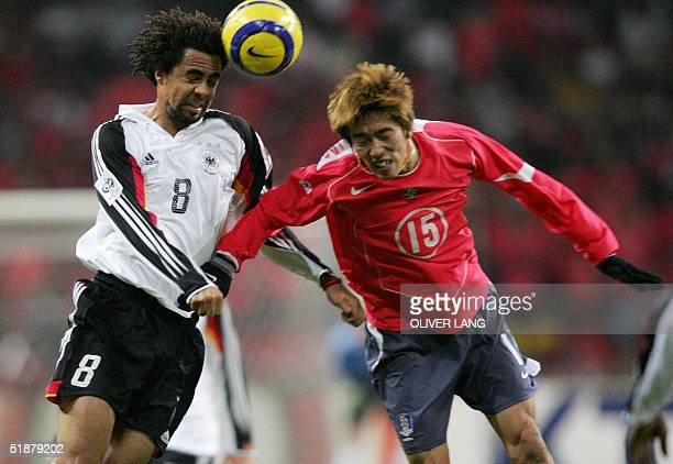 German defender Patrick Owomoyela vies against Korean Jung-Woo Kim 19 December 2004 at the Busan Asiad Main Stadium, during their friendly football...