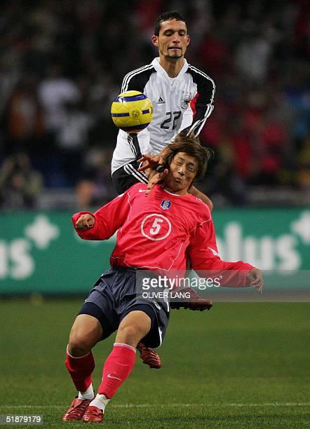 German striker Kevin Kuranyi vies against Korean Jae Hong Kim 19 December 2004 at the Busan Asiad Main Stadium, during their friendly football match....