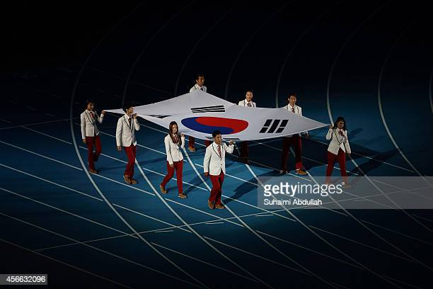 South Korea gold medal athletes carrying the country national flag enter the ground during the closing ceremony on day fifteen of the 2014 Asian...