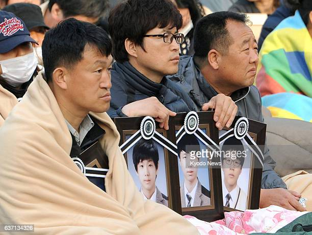 SEOUL South Korea People holding portraits of their children who were victims aboard the sunken ferry Sewol sit near the presidential Blue House in...