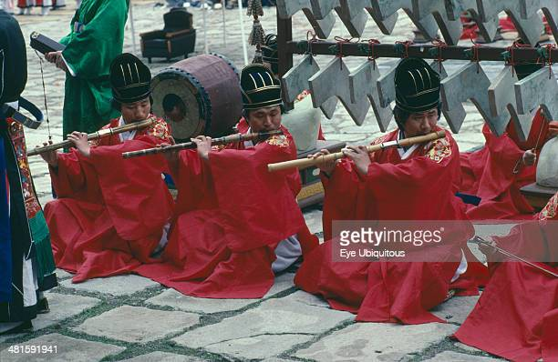 South Korea Religion Buddhism Confucian Rites Orchestra Line of men in red robes sat on ground playing bamboo flutes