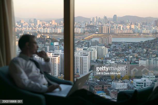 south korea, seoul, kangnam-gu, mature businessman looking out window - south korea stock pictures, royalty-free photos & images