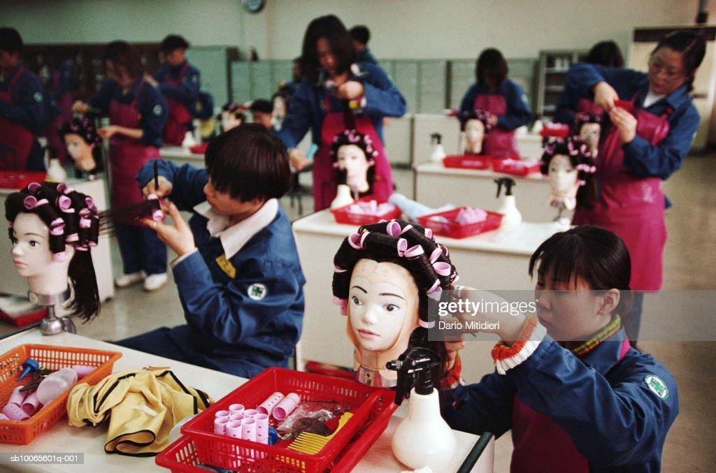 Teenage girls (16-17) in classroom during hairdressing lesson : Fotografia de notícias