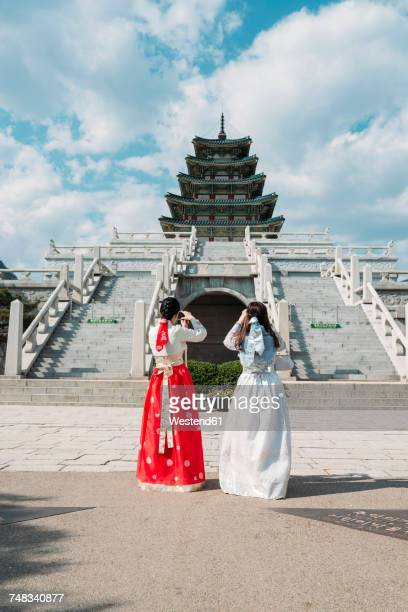 south korea, seoul, tow women wearing traditional korean dresses taking photos of the national folk museum of korea, inside gyeongbokgung palace - gyeongbokgung palace 個照片及圖片檔