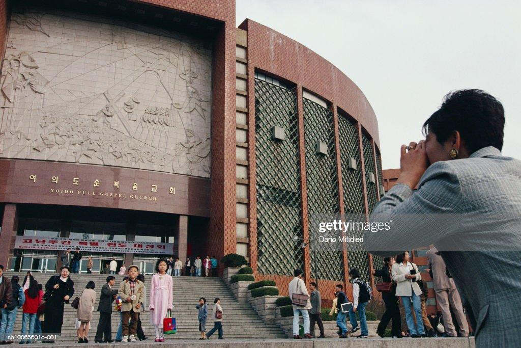 South Korea, Seoul, woman photographing Yoido Full Gospel Church