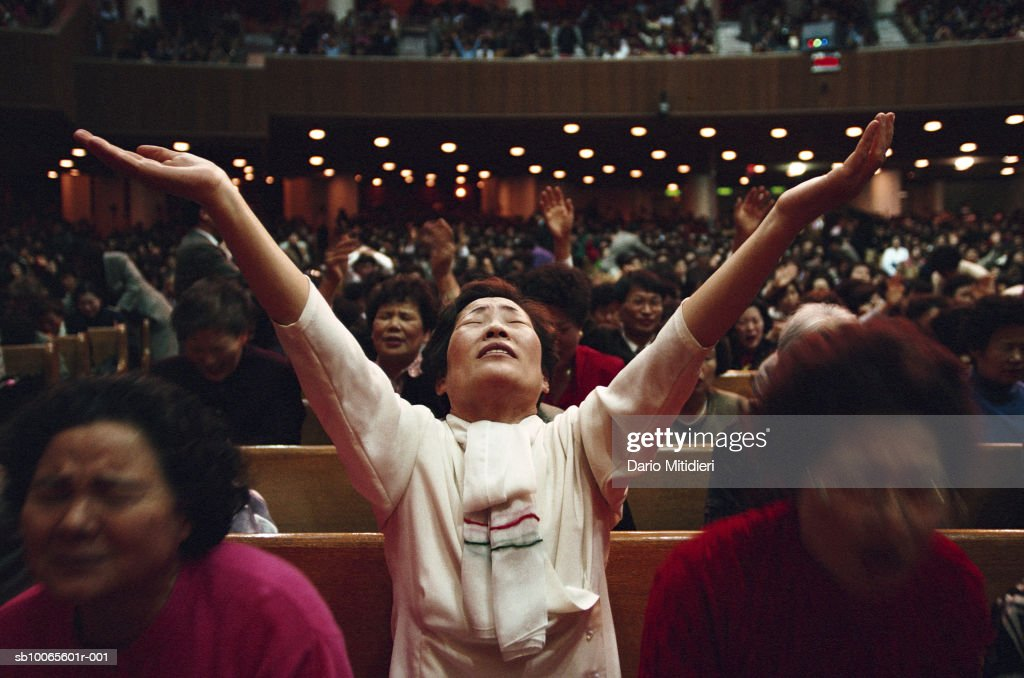 People praying, one woman standing with raised arms : News Photo