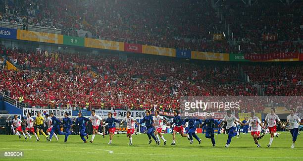 South Korea team run the length of the pitch to celebrate their 2-1 victory after the FIFA World Cup Finals 2002 Second Round match between South...