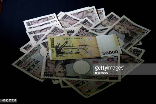 A South Korean 50000 won banknote sits on a pile of Japanese 10000 yen banknotes for a photograph at the Korea Exchange Bank headquarters in Seoul...