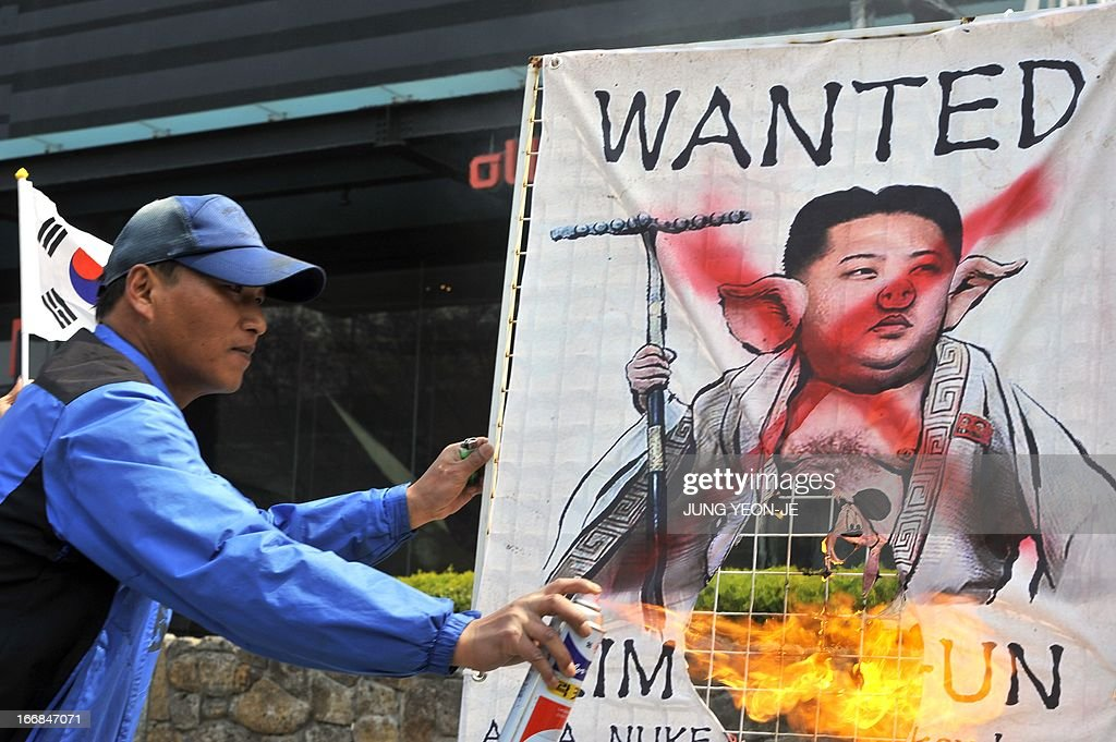 A South Korean activist burns a placard showing a caricature of North Korean leader Kim Jong-Un during an anti-North Korea rally in Seoul on April 18, 2013. North Korea laid out conditions on April 18 for any talks with Seoul or Washington, including the withdrawal of UN sanctions and a guaranteed end to South Korea-US joint military drills.