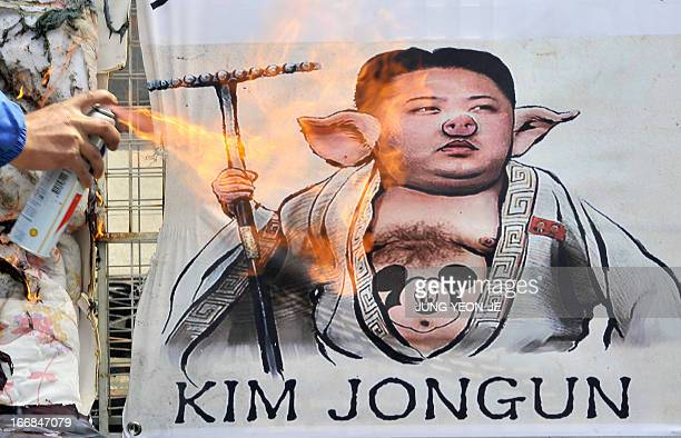 A South Korean activist burns a placard showing a caricature of North Korean leader Kim JongUn during an antiNorth Korea rally in Seoul on April 18...