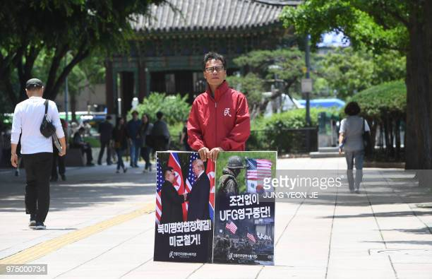 A South Korean activist holds placards showing images of the TrumpKim summit and a South KoreaUS joint military drill during a rally to demand a halt...