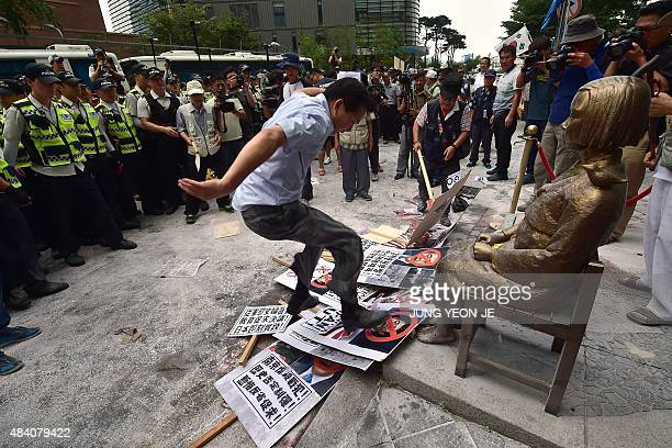 A South Korean activist tramples down on portraits of Japan's Prime Minister Shinzo Abe in front of a statue of a South Korean teenage girl called...