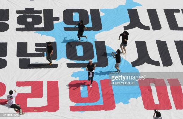 South Korean activists dance on a big 'reunification flag' inscribed with a slogan reading 'The era of peace The era of youth Our future' during a...