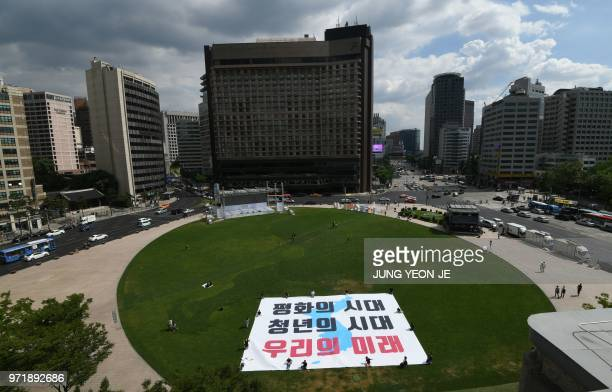 South Korean activists display a big 'reunification flag' inscribed with a slogan reading 'The era of peace The era of youth Our future' during a...