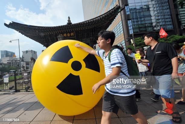 South Korean activists march while rolling a large balloon with a radioactivity warning sign during an antinuclear protest in Seoul on August 6 2013...