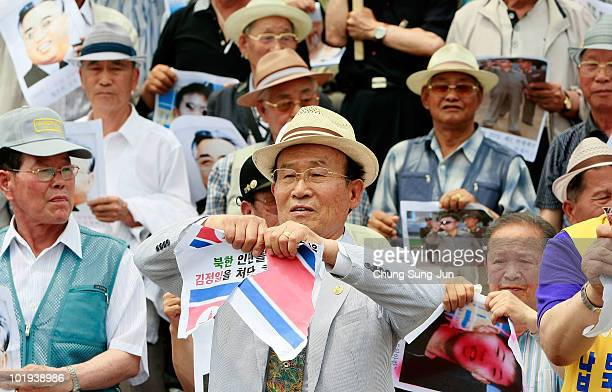 South Korean activists tear North Korean flags before the release of helium balloons carrying 'propaganda' leaflets destined for North Korea on June...