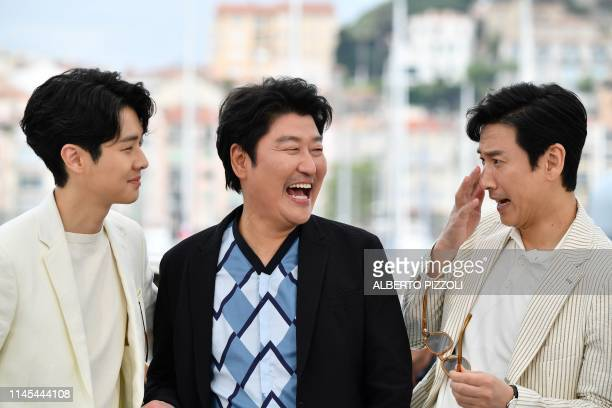 South Korean actor Choi Wooshik South Korean actor Kangho Song and South Korean actor Lee Sunkyun pose during a photocall for the film Parasite at...