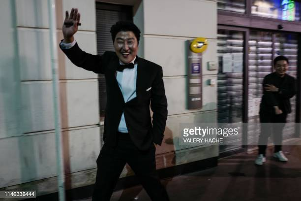 South Korean actor Song Kangho reacts as people congratulate him in a street of Cannes after the film Parasite in which he stars won the Palme d'Or...