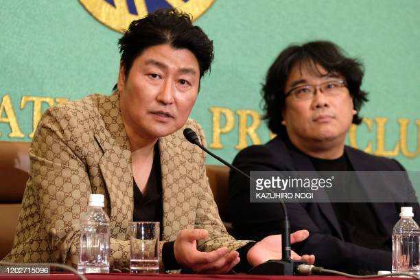 South Korean actor Song Kangho speaks as film director Bong Joonho who directed the film Parasite looks on during a press conference at the Japan...