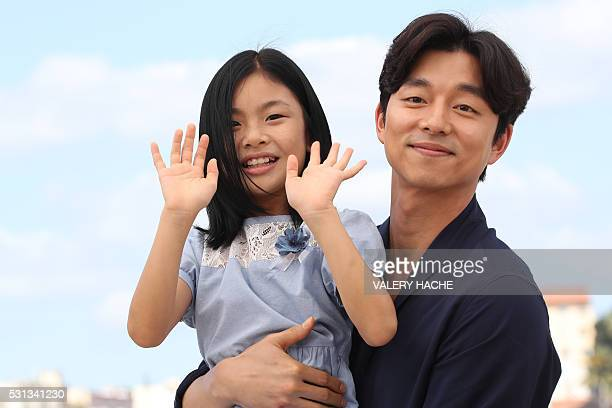 South Korean actress Kim Suan waves on May 14 2016 while posing with South Korean actor Gong Yoo during a photocall for the film 'BuSanHaeng ' at the...